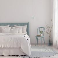 Drevená posteľ v spálni so svetlomodrými doplnkami