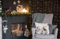 Sivé kreslo s dekoračnými vankúšmi a krb s vianočnými dekoráciami