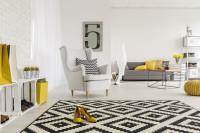 Kreslo ušiak v čierno-bielej obývačke so žltými akcentami