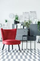 Červené kreslo a kovový odkladací stolík v sivo bielej obývačke
