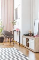 Sivé kreslo a kovový odkladací stôl vo svetlej obývačke