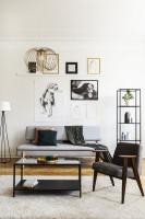 Sivá pohovka a kovový stolík v čierno-bielej obývačke
