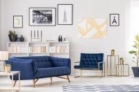 Modrá pohovka a kreslo v obývačke s kolekciou obrazov