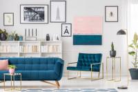 Modrá pohovka a retro kreslo v obývačke s obrazmi na stenách