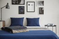 Posteľ s modrými vankúšmi a čiernobiele fotografie