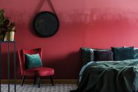 Bordové kreslo a veľký manželská posteľ vo veľkej glamour spálni