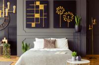 Posteľ a čierno-zlaté obrazy v sivej glamour spálni