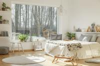 Pohodlná posteľ s pletenou dekou a sivými vankúšmi