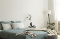 Manželská posteľ a stojanová lampa vo svetlej spálni