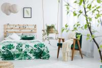 Drevená manželská posteľ a zelené kreslo vo svetlej bohémskej spálni
