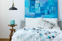 Manželská posteľ v spálni v modro-bielych tónoch