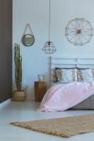 Biela posteľ a veľké nástenné hodiny v romantickej spálni