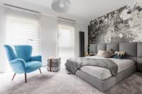 Modré kreslo ušiak a manželská posteľ v modernej spálni