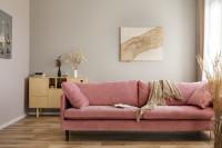 Ružová pohovka vo svetlej obývačke s prírodnými doplnkami