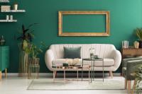 Biela pohovka a kovové stolíky v zelenej glamour obývačke