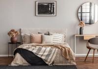 Béžová posteľ a okrúhle zrkadlo nad konzolovým stolíkom