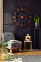 čalúnené kreslo a veľké nástenné hodiny v glamour obývačke