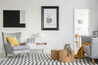 Sivé kreslo ušiak so žltým vankúšom vo svetlej obývačke