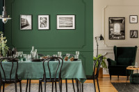 Jedálenský stôl a drevené stoličky v jedálni s tmavozelenou stenou