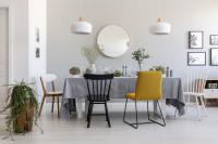 Dlhý jedálenský stôl s obrusom a rôznofarebné stoličky