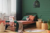 Čierna kovová posteľ v detskej izbe so zelenou stenou