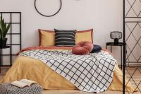 Manželská posteľ v spálni s čiernymi kovovými doplnkami