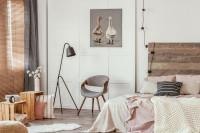 Čierna stojanová lampa a sivé kreslo v útulnej spálni