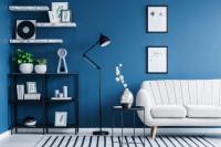 Biela pohovka v kontraste s modrou stenou a čierne doplnky
