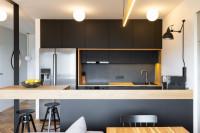 Moderná čierna kuchynská linka s pracovnou doskou zo svetlého dreva
