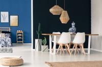 Biele stoličky a bambusové lampy v jedálni s čiernou stenou