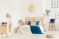 Drevená posteľ a nízka komoda vo svetlej spálni