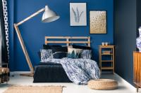 Drevená posteľ a stojanová lampa v spálni s modrou stenou