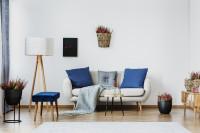 Pohovka s modrými vankúšmi a stojanová lampa