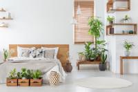 Drevená manželská posteľ v spálni s rastlinnou výzdobou