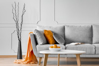 Sivá trojmiestna pohovka s oranžovými doplnkami