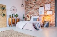 Manželská posteľ v spálni s výraznou tehlovou stenou