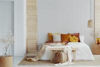 Manželská posteľ s vankúšmi a drevenými doplnkami