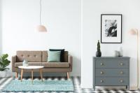 Dvojmiestna pohovka a sivá komoda v škandinávskej obývačke