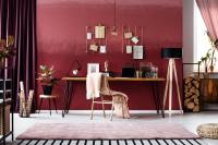 Písací stôl a stojanová lampa v pracovni s bordovou stenou