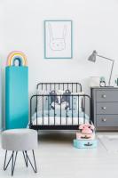 Kovová posteľ a sivá komoda vo svetlej detskej izbe