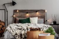 Drevená manželská posteľ s vianočnými dekoráciami a svetelnou reťazou