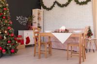 Drevený stôl vo vianočnej jedálni s tabuľovou stenou