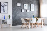 Dlhý drevený stôl a biele jedálenské stoličky v kontraste so sivou stenou