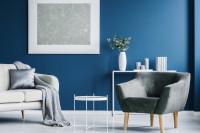Sivé kreslo a biele doplnky v kontraste s modrou stenou