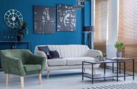 Svetlá retro pohovka v obývačke s výraznou modrou stenou