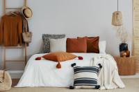 Manželská posteľ v bielej spálni s doplnkami v hrdzavých farbách