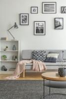 Sivá pohovka s dekoračnou dekou a vankúšmi