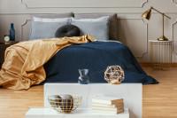 Manželská posteľ s modrou dekou a kovová lampa