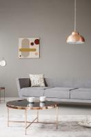 Sivá pohovka a kovový stolík v retro obývačke