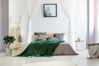 Manželská posteľ s dekoračnými vankúšmi a zelenou dekou